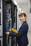 Happy technician using digital cable analyzer on server