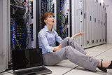 Stressed technician sitting on floor beside open server