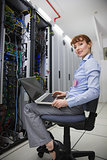 Happy technician sitting on swivel chair using laptop to diagnose servers