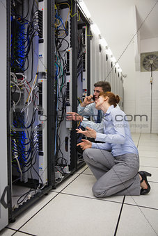 Team of technicians kneeling and looking at servers