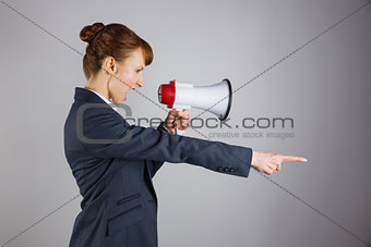 Angry businesswoman shouting through megaphone and pointing