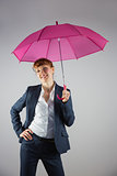 Smiling businesswoman holding pink umbrella