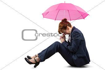 Sitting businesswoman holding pink umbrella