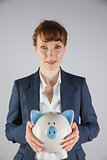 Smiling businesswoman holding piggy bank