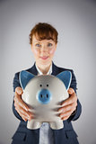 Smiling businesswoman showing piggy bank
