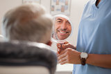 Dentist showing patient his new smile in the mirror