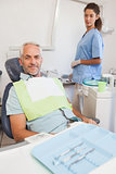 Patient smiling at camera sitting in the chair
