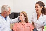 Dentist and assistant smiling with patient in chair