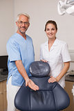 Dentist and assistant smiling at camera inviting you to the chair