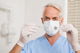 Dentist in surgical mask looking at camera holding tools