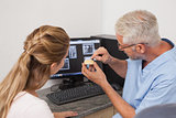 Dentist showing patient model of teeth and xrays