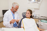 Dentist showing patient model of teeth
