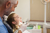 Dentist examining a patients teeth in the dentists chair under bright light