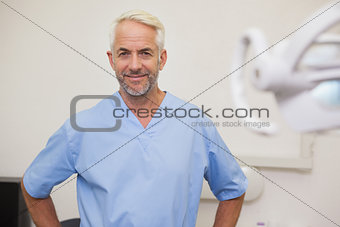 Dentist smiling at camera in blue scrubs