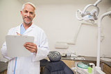 Dentist smiling at camera holding clipboard
