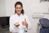 Dentist showing thumbs up and holding mouth model