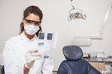 Dentist examining xrays wearing surgical mask