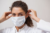 Dentist putting on surgical mask looking at camera
