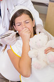 Pediatric dentist trying to see coughing patients teeth