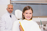 Pediatric dentist and little girl smiling at camera
