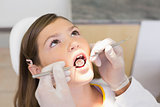 Pediatric dentist examining a little girls teeth in the dentists chair