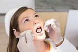 Pediatric dentist examining a little girls teeth in the dentists chair