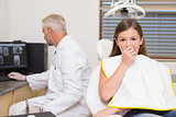 Terrified little girl looking at camera in dentists chair