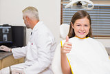 Smiling little girl showing thumbs up in dentists chair