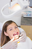 Dentist putting mouth retractor on little girl