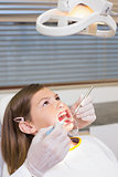 Dentist using mouth retractor on little girl