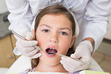 Pediatric dentist examining a patients teeth in the dentists chair