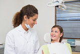 Pediatric dentist smiling with little girl in the chair
