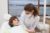 Pediatric dentist smiling down at little boy in chair