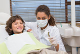 Pediatric dentist showing little boy in chair the drill