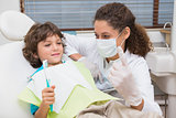 Pediatric dentist showing little boy in chair the toothrbrush
