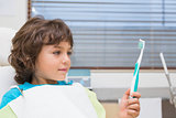Little boy in dentists chair holding toothrbrush