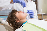 Pediatric dentist examining a little boys teeth in the dentists chair