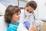 Pediatric dentist showing little boy his teeth in the mirror