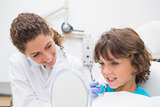 Pediatric dentist showing little boy his teeth in the mirror