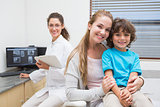 Pediatric dentist smiling at camera with little boy and his mother