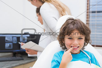 Little boy smiling at camera with mother and dentist in background