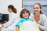 Little boy and mother smiling at camera with dentist in background