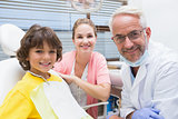 Little boy smiling at camera with mother and dentist beside him