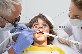 Pediatric dentist and assistant examining a little boys teeth