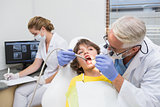 Pediatric dentist examining a little boys teeth with assistant behind