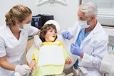 Terrified little boy looking at needle in dentists chair