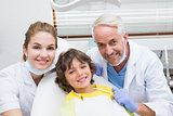 Pediatric dentist assistant and little boy all smiling at camera