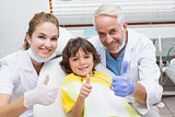 Pediatric dentist assistant and little boy all smiling at camera with thumbs up