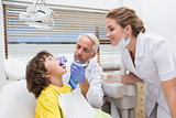 Pediatric dentist examining a little boys teeth with his assistant