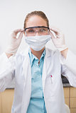 Dentist putting on her protective glasses